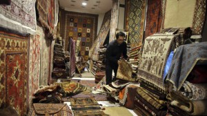 A seller arranges Iranian carpets at his shop in Dubai old market November 24, 2013. Iran's currency jumped more than 3 percent against the U.S. dollar on Sunday as news of a breakthrough deal to curb Tehran's nuclear program raised hopes that the economy would start recovering from international sanctions. Dubai's non-oil trade with Iran has shrunk by over a third in the past 18 months, totaling $2.9 billion in the first half of 2013, according to Dubai customs data. REUTERS/Mohammed Omar (UNITED ARAB EMIRATES - Tags: BUSINESS POLITICS)